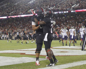 Photo - Stanford's Ty Montgomery, right, celebrates with teammate David Yankey after scoring a touchdown against Washington during the first half of an NCAA college football game in Stanford, Calif., Saturday, Oct. 5, 2013. (AP Photo/George Nikitin)