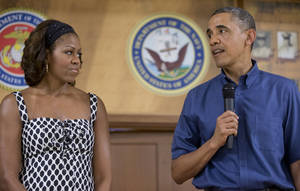 Photo - President Barack Obama and first lady Michelle Obama look to each other as President Obama speaks to members of the military and their families in Anderson Hall at Marine Corps Base Hawaii, Wednesday, Dec. 25, 2013, in Kaneohe Bay, Hawaii. The first family is in Hawaii for a family holiday vacation. (AP Photo/Carolyn Kaster)