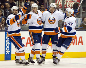 Photo - From left, New York Islanders' Frans Nielsen, Travis Hamonic, Michael Grabner and Andrew MacDonald celebrate a goal against the Toronto Maple Leafs during the third period of their NHL hockey game, Thursday, Jan. 24, 2013, in Toronto. The Islanders won 7-4. (AP Photo/The Canadian Press, Frank Gunn)