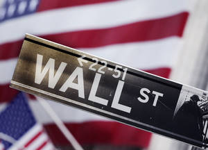 Photo - FILE - This Aug. 9, 2011 photo shows a Wall Street street sign near the New York Stock Exchange, in New York. (AP Photo/Mark Lennihan, File)