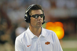 Photo -  Oklahoma State coach Mike Gundy watches his team during the fourth quarter against Texas in an NCAA college football game Saturday, Nov. 16, 2013, in Austin, Texas. Oklahoma State won 38-13. (AP Photo/Michael Thomas)