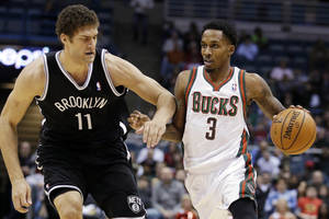 Photo - Milwaukee Bucks' Brandon Jennings (3) drives past Brooklyn Nets' Brook Lopez (11) during the second half of an NBA basketball game, Wednesday, Dec. 26, 2012, in Milwaukee. The Bucks won 108-93. (AP Photo/Morry Gash)