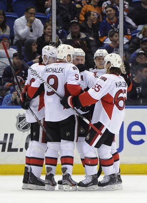 Photo - Ottawa Senators' Milan Michalek (9), Erik Karlsson (65) and teammates celebrate Jason Spezza's goal against the New York Islanders in the second period of an NHL hockey game Tuesday, April 8, 2014, in Uniondale, N.Y. (AP Photo/Kathy Kmonicek)
