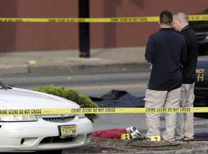 Photo - A person lays on the ground near evidence markers as officials investigate the scene where a Jersey City Police Department officer was shot and killed while responding to a call at a 24-hour pharmacy, Sunday, July 13, 2014, in Jersey City, N.J.  Officer Melvin Santiago was shot in the head while still in his police vehicle as he and his partner responded to an armed robbery call  at about 4.a.m., Jersey City Mayor Steven Fulop said in a statement.  Fulop said officers responding to the robbery call shot and killed the man who shot Santiago. He was not immediately identified.(AP Photo/Julio Cortez)