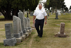 Photo -  Deputy Fire Chief Jim Bailey walks past grave markers near the location of a mass, unmarked gravesite discovered at the IOOF Cemetery in Norman, where the victims of a 1918 fire are believed to be buried. PHOTOs BY STEVE SISNEY, THE OKLAHOMAN  <strong>STEVE SISNEY</strong>