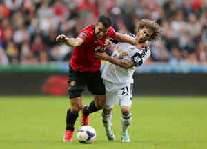 Photo - Manchester United's Robin van Persie, left, and Swansea City's Jose Alberto Canas battle for the ball during the English Premier League soccer match at the Liberty Stadium, Swansea, England, Saturday August 17, 2013. (AP Photo/Nick Potts, PA) UNITED KINGDOM OUT - NO SALES - NO ARCHIVES