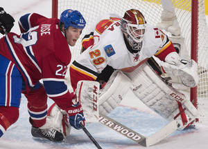 Photo - Montreal Canadiens' Dale Weise, left, moves in on Calgary Flames goaltender Reto Berra during the second period of an NHL hockey game Tuesday, Feb. 4, 2014, in Montreal. (AP Photo/The Canadian Press, Graham Hughes)