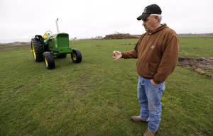 Photo - In this Wednesday, April 10, 2013 photo, farmer Clark Kelly holds a golf ball he dug out of a fairway on the Hend-Co-Hills Golf Course, in Biggsville, Ill. Kelly purchased the course, which was in foreclosure, with plans to plow it into farm land. Across the Midwest, farmers are planting crops on almost any scrap of available land to take advantage of consistently high corn and soybean prices. (AP Photo/Charlie Neibergall)