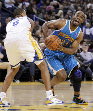 Photo -   New Orleans Hornets forward Carl Landry (24) looks for room around Golden State Warriors forward Dominic McGuire (5) in the first half of an NBA basketball game in Oakland, Calif., Wednesday, March 28, 2012. (AP Photo/Paul Sakuma)