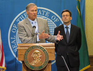 Photo - Washington state Gov. Jay Inslee, left, is joined by state Attorney General Bob Ferguson as he talks to the media in Olympia, Wash. about the federal government's announcement that it will not sue to stop Washington and Colorado from taxing and regulating recreational marijuana for adults, on Thursday, Aug. 29, 2013. Last fall, voters made both states the first in the country to legalize the sale of marijuana to adults over 21 at state-licensed stores. The states are creating rules for the system, with sales expected to begin early next year. (AP Photo/Rachel La Corte)
