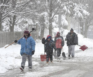 "Photo - From left, Tony Clark, 13, Hezekiah Simmons, 8, Trevelle Wilson, 12, and Kelvin Jones, walk south on State Street in Champaign, Ill., looking for driveways to shovel on Monday, March 25, 2013. A major snowstorm hit the area overnight leaving many roads and driveways impassable. Tony Clark said they had found one job as of 11 a.m., ""we charge $10, for a small one, $20 for medium and $30 for super big"". (AP Photo/News-Gazette, John Dixon) MANDATORY CREDIT"