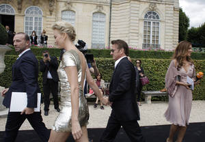 Photo - Actress Charlize Theron and actor Sean Penn arrive hand in hand at Dior's Fall-Winter 2014-2015 Haute Couture fashion collection, in Paris, France, Monday, July 7, 2014. (AP Photo/Thibault Camus)