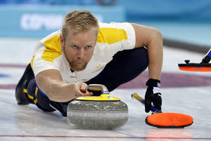 Photo - Sweden's skip Niklas Edin delivers the rock during men's curling competition against Canada at the 2014 Winter Olympics, Tuesday, Feb. 11, 2014, in Sochi, Russia. (AP Photo/Robert F. Bukaty)