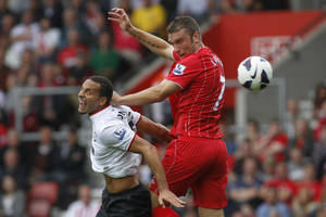 Photo -   Southampton's Rickie Lambert, right, competes with Manchester United's Rio Ferdinand during their English Premier League soccer match at St Mary's stadium, Southampton, England, Sunday, Sept. 2, 2012. (AP Photo/Sang Tan)