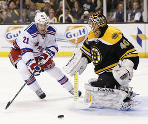 photo - New York Rangers' Derek Stepan (21) skates for the rebound off Boston Bruins goalie Tuukka Rask (40), of Finland, during the first period of an NHL hockey game in Boston, Saturday, Jan. 19, 2013. (AP Photo/Michael Dwyer)