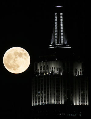 photo -   A full moon rises near the Empire State Building, as seen from Hoboken, N.J., Wednesday, Nov. 28, 2012. (AP Photo/Julio Cortez)