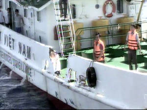Photo - In this video image released by Vietnam Coast Guard, Vietnamese surveillance ship crew members stand near the side of the ship, allegedly damaged after being rammed by a Chinese ship, in the South China Sea, off Vietnam's coast, Wednesday, May 7, 2014. Chinese ships have been ramming into and firing water cannons at Vietnamese vessels trying to stop Beijing from putting an oil rig in the South China Sea, according to officials and video footage Wednesday, in a dangerous escalation of tensions over waters considered a global flashpoint. (AP Photo/Vietnam Coast Guard)