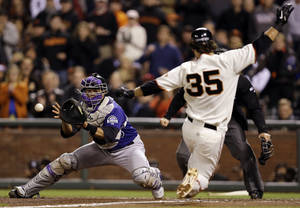 Photo -   Colorado Rockies catcher Wilin Rosario, left, catches the relay from the outfield and tags out San Francisco Giants' Brandon Crawford, who was trying to score on a single from Angel Pagan, during the fifth inning of a baseball game on Monday, Sept. 17, 2012, in San Francisco. (AP Photo/Marcio Jose Sanchez)