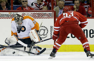 Photo - Philadelphia Flyers goalie Steve Mason (35) deflects a shot on goal by Carolina Hurricanes' Jeff Skinner (53)during the first period of an NHL hockey game in Raleigh, N.C., Sunday, Oct. 6, 2013. (AP Photo/Gerry Broome)