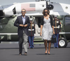 Photo - President Barack Obama and first lady Michelle Obama walk across the tarmac before their departure on Air Force One at Homestead Air Reserve Base, Sunday, March 9, 2014, in Homestead, Fla. Obama returned to Washington after spending the weekend in Florida. (AP Photo/Pablo Martinez Monsivais)
