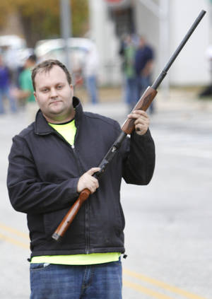 Photo - Joseph Hughes fires a shotgun to start the Turkey Trot fun run.