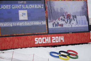 Photo - A large screen announces a brief snow delay in the start of the second run of the women's giant slalom at the Sochi 2014 Winter Olympics, Tuesday, Feb. 18, 2014, in Krasnaya Polyana, Russia. (AP Photo/Gero Breloer)