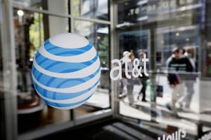 Photo - FILE - This Wednesday, Oct. 17, 2012, file photo shows an AT&T logo on an AT&T Wireless retail store front, in Philadelphia. AT&T reports quarterly earnings on Tuesday, April 22, 2014. (AP Photo/Matt Rourke, File)