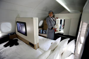 """Photo - An Etihad Airways official stands inside the 125-square-foot (11.61-square-meter) area that includes a """"living room"""" partitioned off from the first-class aisle, leather seating, a chilled minibar and a 32-inch flat-screen TV, at a training facility in Abu Dhabi, United Arab Emirates, Sunday, May 4, 2014. Etihad Airways, a fast-growing Mideast carrier, laid out plans Sunday to offer passengers who find first-class seats a bit too tight a miniature suite featuring a closed-off bedroom, private bathroom and a dedicated butler. (AP Photo/Kamran Jebreili)"""