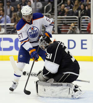 Photo - Edmonton Oilers' David Perron, left, tries to score past Los Angeles Kings goaltender Martin Jones, right, during the first period of an NHL hockey game in Los Angeles, Tuesday, Dec. 17, 2013. (AP Photo/Danny Moloshok)