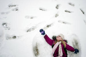 Photo - In a Feb. 28, 2013 photo, kindergartener Paige Chisholm, 6, makes a snow angel during at Cook Elementary School in Grand Blanc, Mich. Getting a snow day from school is a bonus for students, but not if they have too many in one year. Schools in northern Michigan may have to extend classes later into June as winter weather led to more cancellations than usual. A bill approved 34-1 Thursday by the Michigan Senate would let schools lengthen their days for the rest of the school year instead of having to make them up. (AP Photo/The Flint Journal, Jake May, FILE)