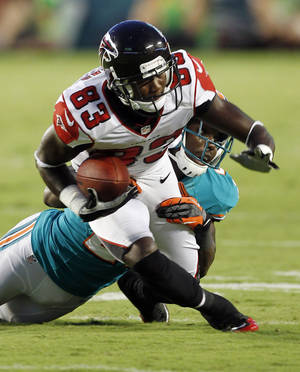 Photo -   Atlanta Falcons wide receiver Harry Douglas (83) is tackled by Miami Dolphins defensive back Vontae Davis during the first half of an NFL preseason football game on Friday, Aug. 24, 2012, in Miami. (AP Photo/Alan Diaz)