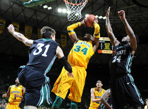 photo - Baylor's Cory Jefferson (34) shoots past South Carolina-Upstate's Mario Blessing (31) and Jodd Maxey during the first half of an NCAA college basketball game, Monday, Dec. 17, 2012, in Waco, Texas. (AP Photo/Waco Tribune Herald, Rod Aydelotte)