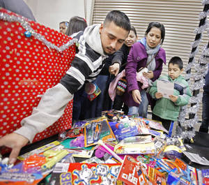Photo - Left: Volunteer Juan Lopez assists as Amelia Rios and Luis Cerna pick out presents at last year's Red Andrews Christmas Dinner.  Photos by Steve Sisney,  The Oklahoman Archives