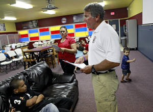 Photo - Retired Oklahoma City police Capt. Phil Carr talks with children and their parents during an orientation class. PHOTO BY JOHN CLANTON, THE OKLAHOMAN