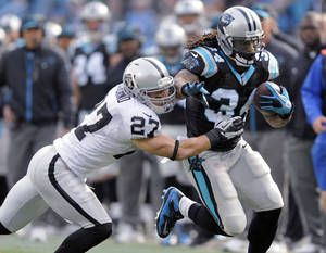 Photo - Carolina Panthers' DeAngelo Williams (34) runs as Oakland Raiders' Matt Giordano (27) tries to make the tackle during the first half of an NFL football game in Charlotte, N.C., Sunday, Dec. 23, 2012. (AP Photo/Mike McCarn)