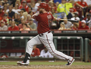 Photo - Arizona Diamondbacks' Jason Kubel hits a two-run single against Cincinnati Reds starting pitcher Mike Leake in the fifth during a baseball game on Wednesday, Aug. 21, 2013, in Cincinnati. (AP Photo/David Kohl)