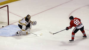 Photo - Chicago Blackhawks' Patrick Kane, right, scores against Boston Bruins goalie Tuukka Rask during the shootout of an NHL hockey game in Chicago, Sunday, Jan. 19, 2014. The Blackhawks won 3-2. (AP Photo/Nam Y. Huh)