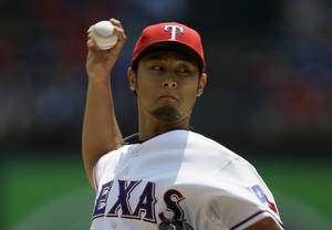 Photo - Texas Rangers starting pitcher Yu Darvish, of Japan, works against the Seattle Mariners in the first inning of a baseball game on Sunday, Aug. 18, 2013, in Arlington, Texas. (AP Photo/Tony Gutierrez)
