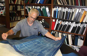 Photo - In this June 19, 2014 photo provided by Robert Gibson, shows Robert Gibson, the emergency section supervisor at the DNR's Department of Mines and Minerals, looking at maps of old coal mines at Southern Illinois University Edwardsville, in Edwardsville, Ill., that are being digitized and  by the state. Mine maps marked the locations of rooms, pillars and shafts _ necessary then and a valuable tool for state officials, homeowners and developers today because of the damage current structures can sustain if an abandoned mine begins to collapse or sag. But the DNR only has about 2,000 maps for the more than 4,000 separate mines that operated in the state, Gibson said. The state is digitizing those in its archives before they deteriorate, but also is searching for as many missing maps as possible. (AP Photo/Courtesy of Robert Gibson,Darlene Barker