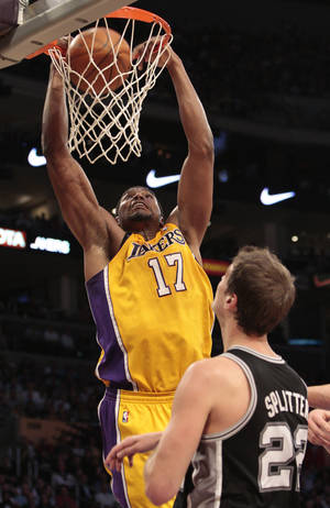 Photo -   Los Angeles Lakers center Andrew Bynum (17) dunks as San Antonio Spurs' Tiago Splitter (22) looks on during the first half of their NBA basketball game, Tuesday, April 17, 2012, in Los Angeles. (AP Photo/Jason Redmond)