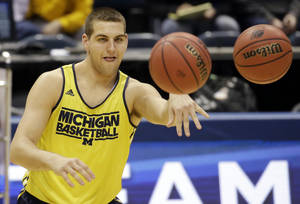 Photo - Michigan forward Mitch McGary passes the balls during a practice session for their NCAA college basketball tournament game Wednesday, March 19, 2014, in Milwaukee. Michigan plays Wofford on Thursday. (AP Photo/Morry Gash)