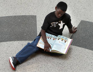 Photo - Carl Albert Middle School student Caleb Collins reads a book before Whiz Kids participants, Carl Albert Middle School students and members of the 2012 Leadership Oklahoma Young Adult Leaders (LOYAL) class, perform a flash mob dance at Ronald J. Norick Downtown LIbrary in Oklahoma City. Photo by Sarah Phipps, The Oklahoman <strong>SARAH PHIPPS</strong>