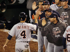 Photo -   Detroit Tigers Omar Infante celebrates with the dugout after he scored on a single by Avisail Garcia in the eighth inning of Game 4 of an American League division baseball series against the Oakland Athletics in Oakland, Calif., Wednesday, Oct. 10, 2012. (AP Photo/Eric Risberg)