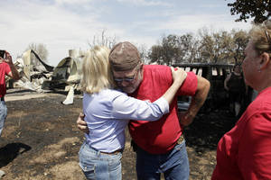 Photo -   Gov. Mary Fallin, left, hugs James Sparr who lost his home and busines, in the background, after wildfires burned across the state in Mannford, Okla., Sunday, Aug. 5, 2012. (AP Photo/Tulsa World, Mike Simons)