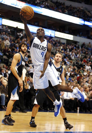 Photo - Dallas Mavericks guard Darren Collison (4) shoots as Minnesota Timberwolves guards Ricky Rubio, left, of Spain, and Jose Juan Barea watch during the second half of an NBA basketball game, Monday, Jan. 14, 2013, in Dallas. The Mavericks won 113-98. (AP Photo/Sharon Ellman)