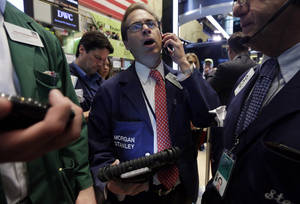 Photo - Trader Dudley Devine, center, works on the floor of the New York Stock Exchange, Friday, July 18, 2014. U.S. stocks are opening higher after Google, Honeywell and other big companies report their quarterly results. (AP Photo/Richard Drew)