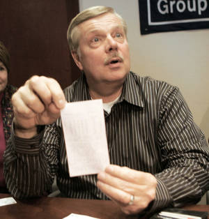 Photo - Bob Space, 60, of Toms River, N.J., holds up the $216 million winning Mega Millions lottery ticket during a news conference Wednesday at Chubb Insurance Co. in Whitehouse Station, N.J. Space and nine co-workers at Chubb will share the jackpot. AP PHOTO