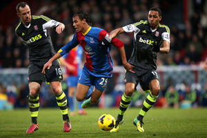 Photo - Crystal Palace's Marouane Chamakh, center, takes a tumble under the challenge of Stoke City's Charlie Adam, left, and Steven N'Zonzi, right, during their English Premier League soccer match at Selhurst Park, London, Saturday, Jan. 18, 2014. (AP Photo/John Walton, PA Wire)   UNITED KINGDOM OUT  -  NO SALES  -  NO ARCHIVES