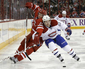 Photo - Carolina Hurricanes' Drayson Bowman (21) and Montreal Canadiens' David Desharnais (51) chase the puck during the second period of an NHL hockey game in Raleigh, N.C., Saturday, Feb. 8, 2014. (AP Photo/Gerry Broome)