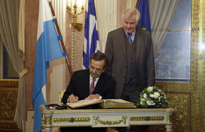 photo - Greek Prime Minister Antonis Samaras, left, flanked by Bavarian state governor Horst Seehofer, background, signs the visitors guest book during his visit in Munich, southern Germany, Sunday, Dec. 9, 2012. (AP Photo/Matthias Schrader)